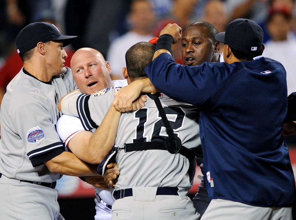 . New York Yankees catcher Ivan Rodriguez (12)  is held back by Los Angeles Angels pitching coach Mike Butcher, second from left, and Angels Gary Matthews Jr. during the sixth inning of a baseball game after a brawl between Rodriguez and Angels Torii Hunter in Anaheim, Calif., Monday Sept. 8, 2008. (AP Photo/Kevork Djansezian)