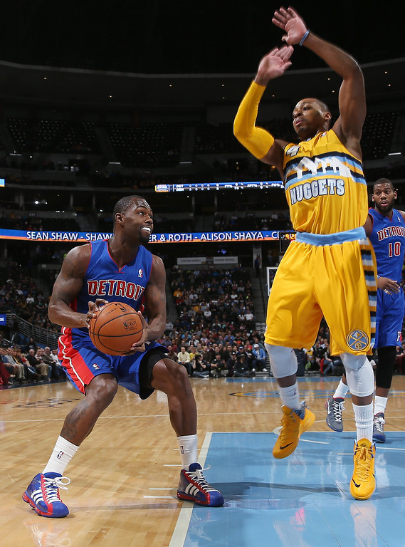 . Detroit Pistons guard Rodney Stuckey, left, dodges the attempted block by Denver Nuggets guard Randy Foye in the first quarter of an NBA basketball game in Denver on Wednesday, March 19, 2014. (AP Photo/David Zalubowski)