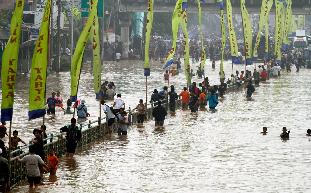 Description of . Indonesians wade through floodwaters in Jakarta, Indonesia, Wednesday, Jan. 16, 2013. Flooding caused by monsoon rains have forced thousands of people to flee their homes in Indonesia\'s capital.  (AP Photo/Achmad Ibrahim)