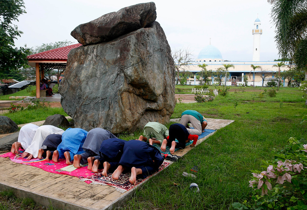 . Filipino Muslims pray to celebrate the end of the holy month of Ramadan known as Eid al-Fitr Friday, June 15, 2018 at the Blue Mosque, background, in suburban Taguig city, east of Manila, Philippines. Muslims all over the world mark Eid al-Fitr with prayers, family reunions and gift-givings. (AP Photo/Bullit Marquez)