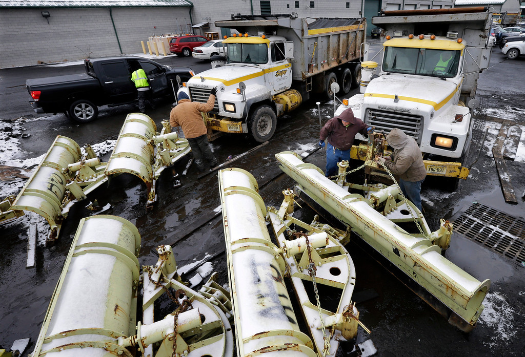. Workers attach snow plows to trucks at a New Jersey Dept. of Transportation maintenance yard, Monday, Jan. 26, 2015, in Newark, N.J. New Jersey Gov. Chris Christie declared a state of emergency saying NJ Transit will shut down late Monday as a winter storm threatens to dump as much as two feet of snow over parts of the state. (AP Photo/Mel Evans)