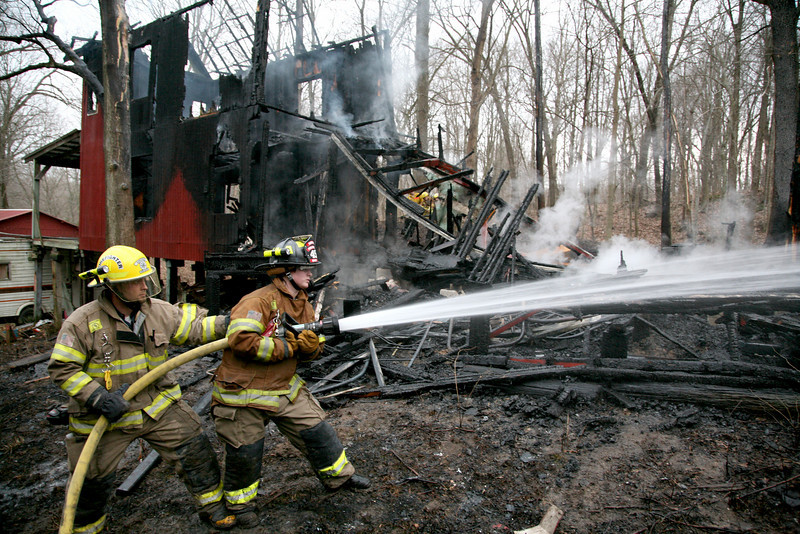 Greenup fire fighters Chris Daugherty and Sarah Wright use a fire hose to douse the remaining hot spots at a fire located at 450 County Road 1650 E in rural Greenup on Monday, March 9, 2009. (Jay Grabiec)