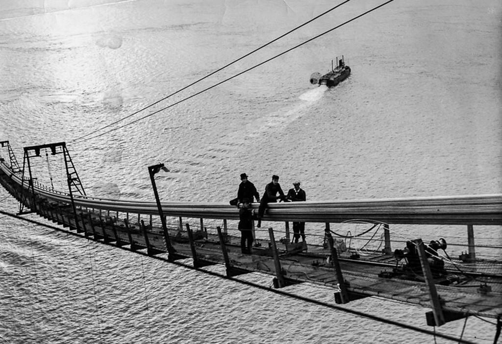 . 1935 - Workmen on catwalk band cables. (Oakland Tribune Photo)