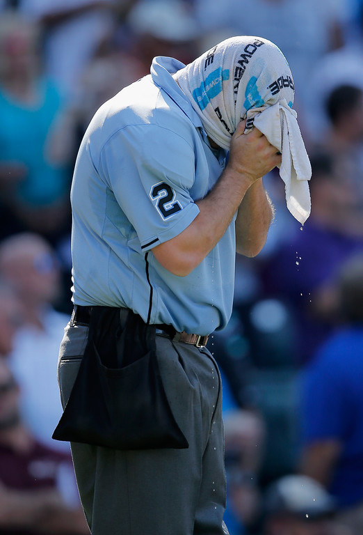 . DENVER, CO - SEPTEMBER 17:  Homeplate umpire Dan Bellino gets some relief from the heat with a wet towel between innings as the Los Angeles Dodgers face the Colorado Rockies at Coors Field on September 17, 2014 in Denver, Colorado. The Rockies defeated the Dodgers 16-2.  (Photo by Doug Pensinger/Getty Images)