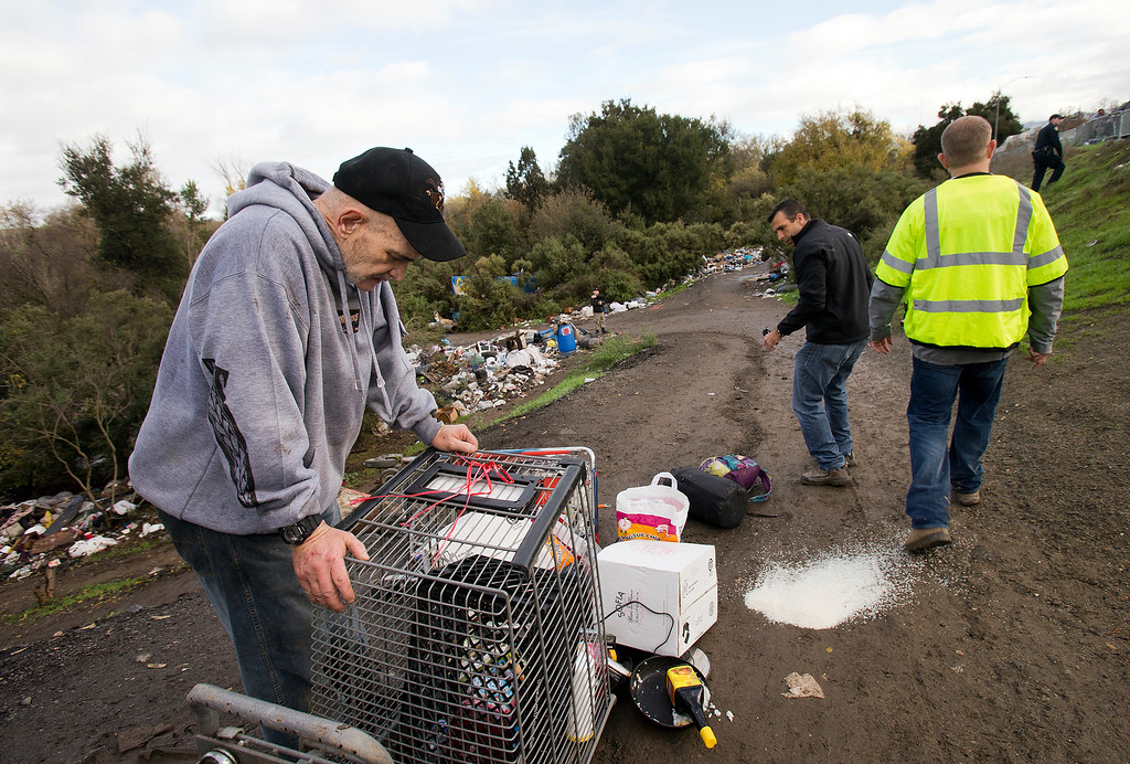 . Andrew Costa, left, who was living in the The Jungle, reacts after a shopping cart full of his possessions topples over as he and San Jose mayor-elect Sam Liccardo (background center) were moving them out of the homeless encampment in San Jose, Calif., on Thursday, Dec. 4, 2014. (LiPo Ching/Bay Area News Group)