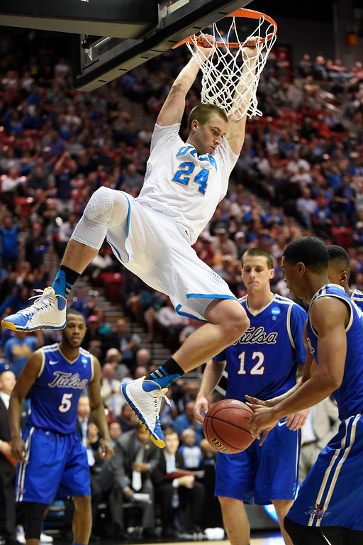 . UCLA forward Travis Wear, above, hangs on the rim after dunking a basket against Tulsa during the second half of a second-round game in the NCAA college basketball tournament Friday, March 21, 2014, in San Diego. (AP Photo/Denis Poroy)