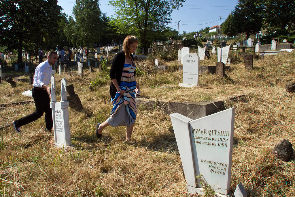 . Kosovo Albanian Muslims visit a cemetery during the holiday of Eid al-Fitr in the ethnically divided northern Kosovo town of Mitrovica, Kosovo, Thursday, Aug. 8, 2013. About a hundred ethnic Albanian Muslims were escorted by police early Thursday into the Serb run part of the town of Mitrovica to visit graves of family and loved ones, a custom marking Eid celebrations. Mitrovica was split into the northern part controlled by Serbs and the southern part run by Albanians at the end of the 1998-99 Kosovo war. Since then the two sides have lived apart and in enmity. Ethnic Albanian Muslims visit the graveyard in the north twice a year, on religious holidays. Serbs from the north also need escorts to visit graves in the southern part. (AP Photo/Visar Kryeziu)