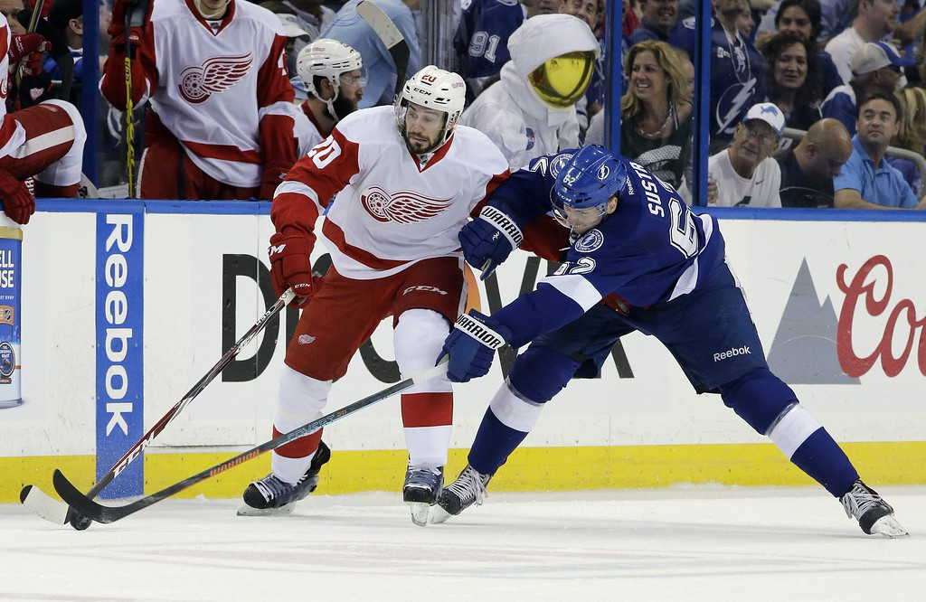 . Detroit Red Wings left wing Drew Miller (20) and Tampa Bay Lightning defenseman Andrej Sustr, of the Czech Republic, battle for the puck during the first period of Game 7 of a first-round NHL Stanley Cup hockey playoff series Wednesday, April 29, 2015, in Tampa, Fla. (AP Photo/Chris O\'Meara)