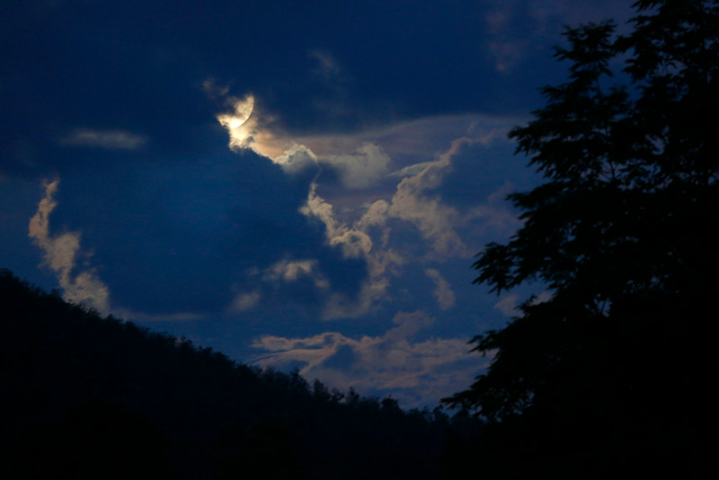 . The full moon peeks through the clouds over forest near Sarajevo,Bosnia, on  Saturday, July 12 2014. The so-called super moon appeared up to 14 percent larger than normal as it\'s orbit is at it\'s closest point to earth. AP Photo/Amel Emric)