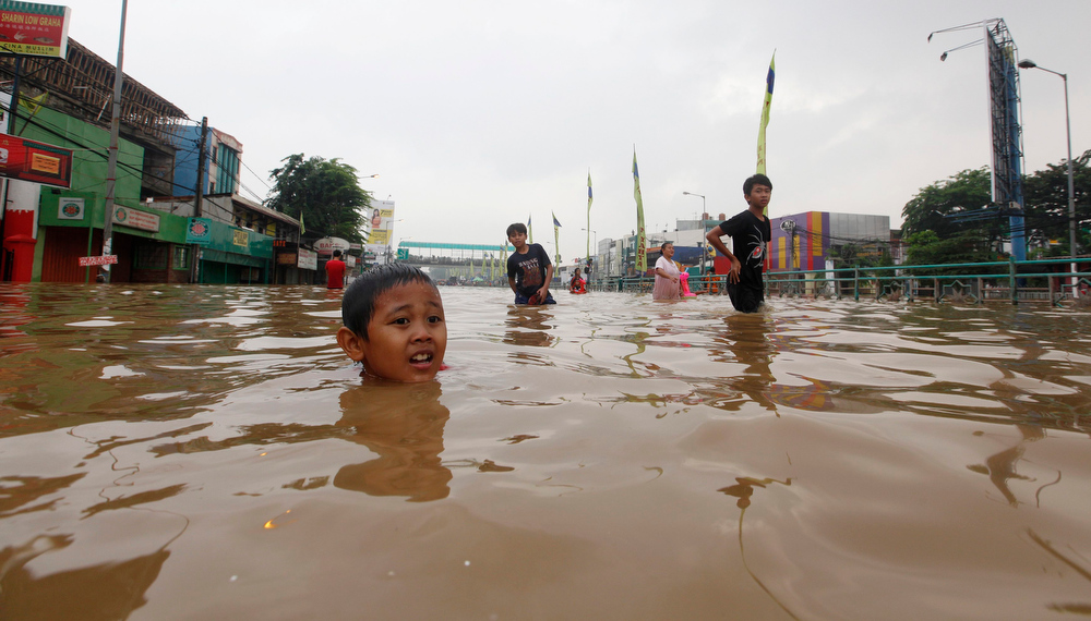 Description of . A boy plays in a flooded road in Jakarta January 16, 2013. Thousands of residents are being evacuated after floods inundated several areas of Jakarta due to the overflow of the Ciliwung River and several days of heavy rains in the capital city, local media reported on Wednesday.   REUTERS/Enny Nuraheni
