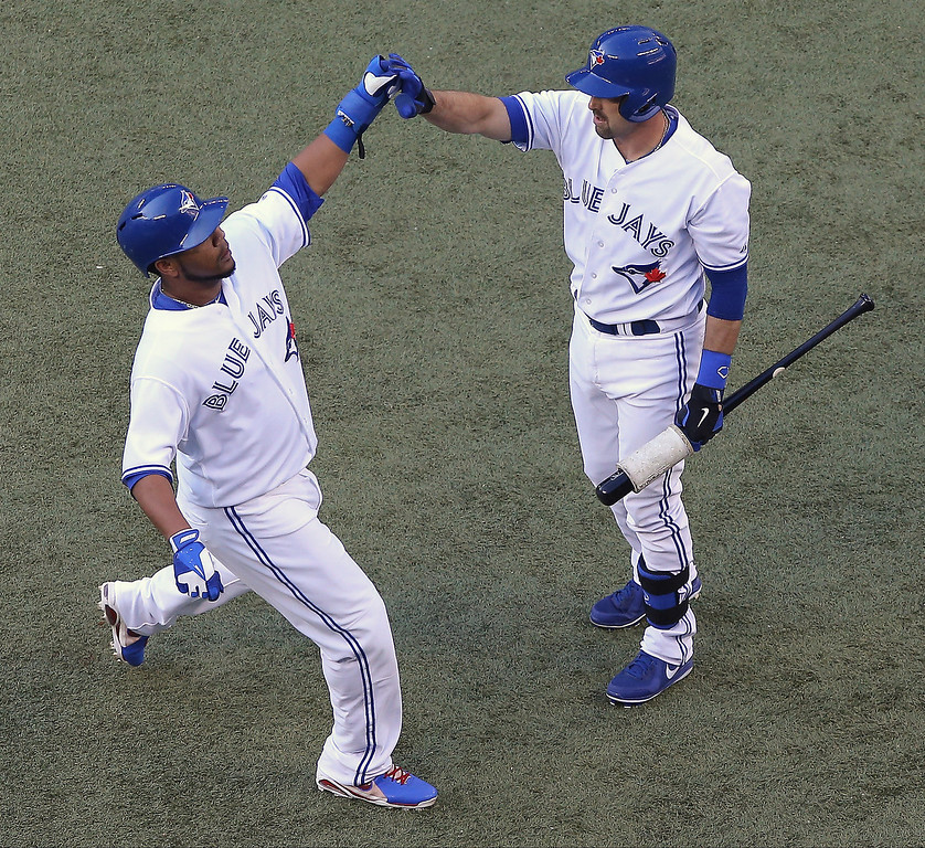 . Edwin Encarnacion #10 of the Toronto Blue Jays is congratulated by Mark DeRosa #16 after scoring a run in the first inning during MLB game action against the Colorado Rockies on June 18, 2013 at Rogers Centre in Toronto, Ontario, Canada. (Photo by Tom Szczerbowski/Getty Images)