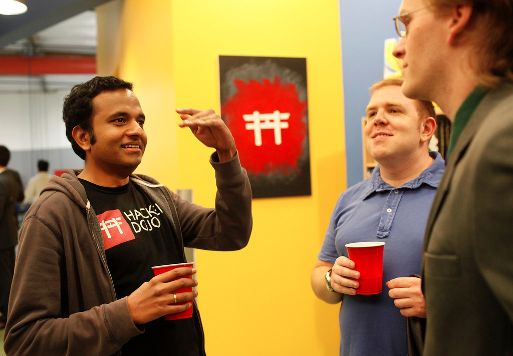 . Prasanth Ram, left, and Ryan Park, right, attend the grand opening of the new Hacker Dojo, a community center for startups, at 599 Fairchild Drive in Mountain View on Wednesday, Feb. 27, 2013. Hacker Dojo faced possible closure after city officials mandated the group bring the 140 S. Whisman Road warehouse it was originally in up to code. The group moved to its new Fairchild Drive home, about five minutes away. For more information about Hacker Dojo, visit http://www.hackerdojo.com. (Kirstina Sangsahachart/ Daily News)