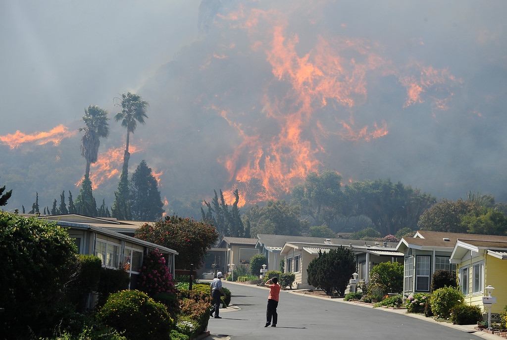 . May 2,2013. Camarillo CA. Local neighbors look at huge flames at the Camarillo Springs mobile home park as strong winds and thick brush, the Springs Fire has blazed through more than 7,000 acres in Camarillo, threatening homes and schools as the fire pushes forward toward the coast.  The Ventura County Fire Department said the Springs Fire broke out at 6:45 a.m. Thursday along the 101 freeway, 50 miles west of downtown Los Angeles, and has damaged a storage facility as well as some homes.   Photo by Gene Blevins/LA DailyNews