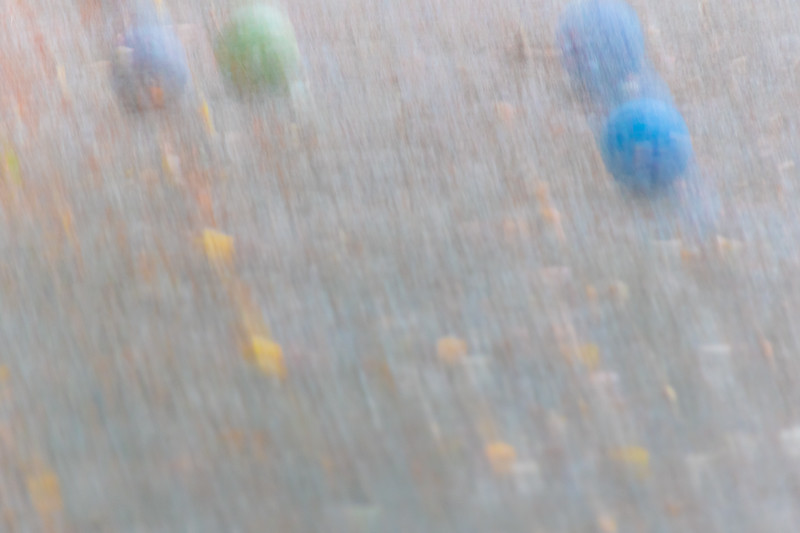 Abstracted and blurred bocce balls appear to be in motion on a sand court
