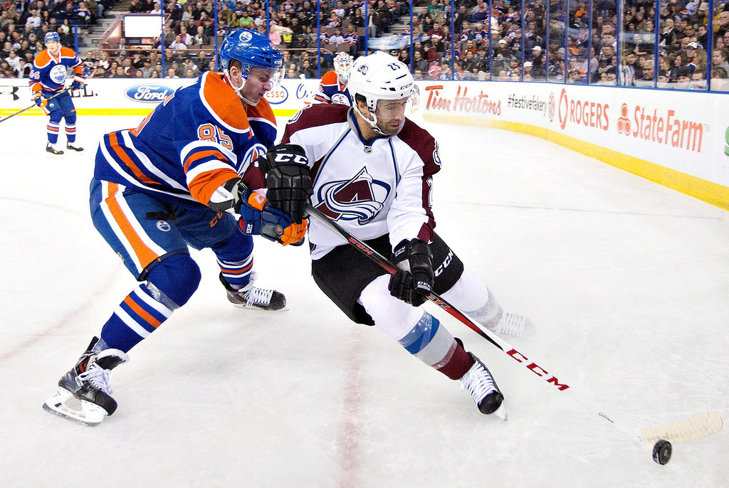 . Colorado Avalanche\'s Maxime Talbot (25) battles in the corner with Edmonton Oilers\' Martin Marincin (85) during first-period NHL hockey game action in Edmonton, Alberta, Thursday, Dec. 5, 2013. (AP Photo/The Canadian Press, Jason Franson)