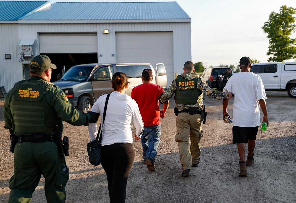 . Government agents take suspects into custody during an immigration sting at Corso\'s Flower and Garden Center, Tuesday, June 5, 2018, in Castalia, Ohio. The operation is one of the largest against employers in recent years on allegations of violating immigration laws. (AP Photo/John Minchillo)