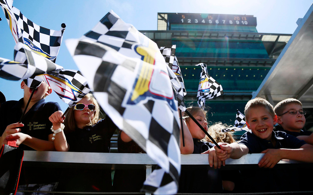 . School children wave checkered flags in front of the Pagoda building during a practice session at the Indianapolis Motor Speedway in Indianapolis, Indiana May 15, 2013. The 97th running of the Indianapolis 500 is scheduled for May 26.  REUTERS/Brent Smith