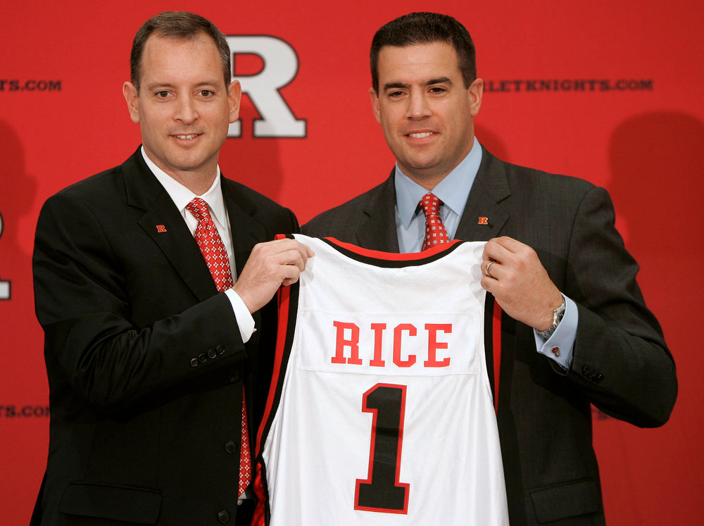 . Rutgers athletic director Tim Pernetti, right, presents Mike Rice with a jersey after Rice was introduced as the school\'s men\'s basketball coach during a news conference in Piscataway, N.J on May 6, 2010. The airing Tuesday, April 2, 2013, of a videotape of Rice using gay slurs, shoving and grabbing his players and throwing balls at them in practice over the past three seasons has Pernetti reconsidering his decision not to fire the coach. Pernetti was given a copy of the video in late November by a disgruntled former employee, and he suspended Rice for three games, fined him $50,000 and made him undergo anger management classes for inappropriate behavior after investigating it. (AP Photo/Rich Schultz, File)