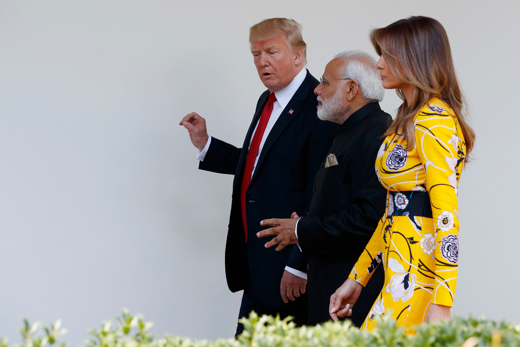 . FILE - In this June 26, 2017 file photo, President Donald Trump and first lady Melania Trump walk with Indian Prime Minister Narendra Modi at the White House in Washington.  Melania Trump has been unafraid to go against her husband�s �America First� agenda, and stay true to her roots, if there�s a message to be taken from her bold, foreign-flavored first lady wardrobe in 2017.   She is wearing a yellow floral Pucci dress.  (AP Photo/Evan Vucci)