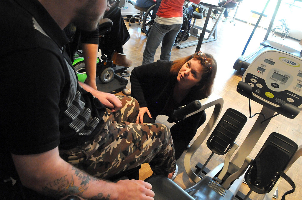 . Mom Cheryl Young adjusts Zack Mohs\' leg as he works out on a sitting step exerciser. (Pioneer Press: John Doman)