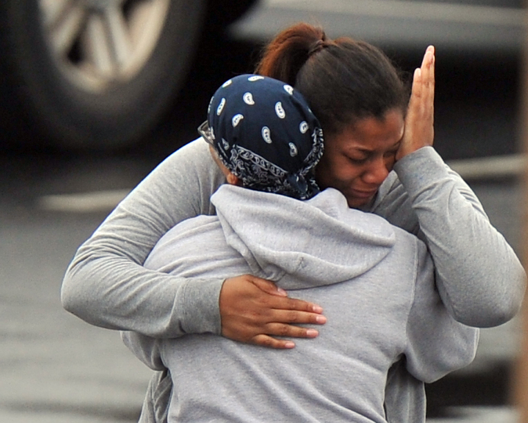 """. FedEx Employees and family members gather a skating rink following a shooting at the FedEx facility in Kennesaw, Ga., on Tuesday, April 29, 2014.  A shooter described as being armed with an assault rifle and having bullets strapped across his chest \""""like Rambo\"""" opened fire Tuesday morning at a FedEx station outside Atlanta, wounding at least six people before police found the suspect dead from an apparent self-inflicted gunshot.  (AP Photo/Atlanta Journal-Constitution, Brant Sanderlin)"""