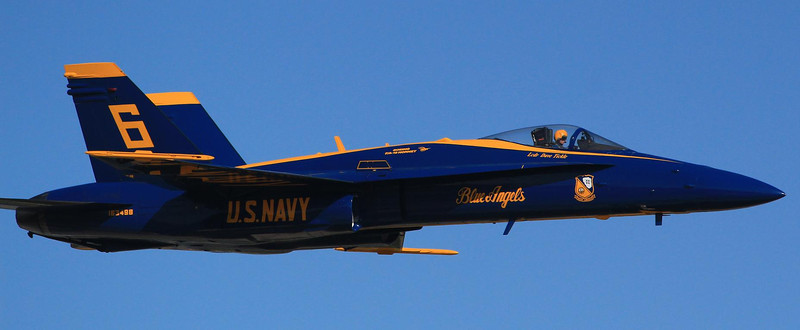 Soloist Dave Tickle makes a high speed pass southbound. Tickle has his lips pulled tight, a common reaction to the exercises used to prevent blackouts. Blue Angels do not use G-suits and rely on abdominal tightening and breathing exercises to keep blood from draining out of the head during high G maneuvers.