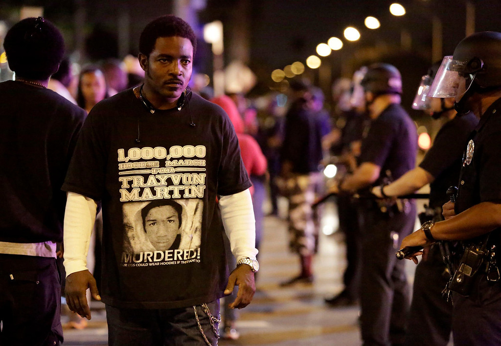 . A protester (L) walks past a line of Los Angeles Police officers as they try to remove protesters from the intersection of Exposition and Crenshaw boulevards, following the George Zimmerman verdict, in Los Angeles, California July 13, 2013. A Florida jury acquitted Zimmerman on Saturday for the shooting death of unarmed black teenager Trayvon Martin, setting free a man who had become a polarizing figure in the national debate over racial profiling and self-defense laws. REUTERS/Jason Redmond