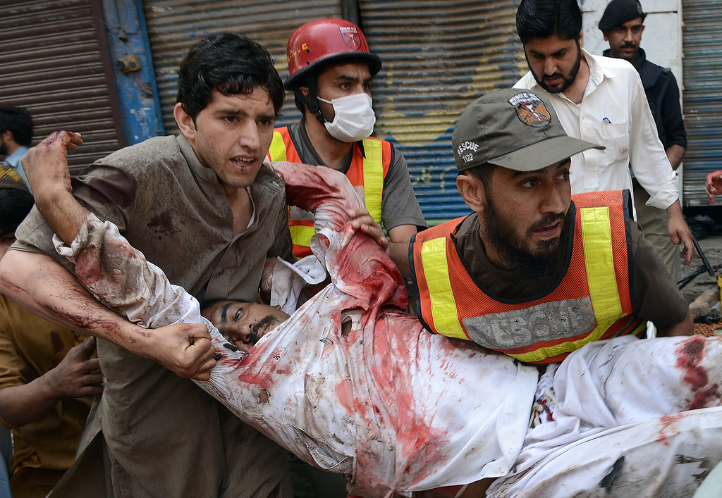 . Pakistani volunteers carry an injured blast victim at the site of a bomb explosion in the busy Kissa Khwani market in Peshawar on September 29, 2013.   AFP PHOTO / A. MAJEED/AFP/Getty Images