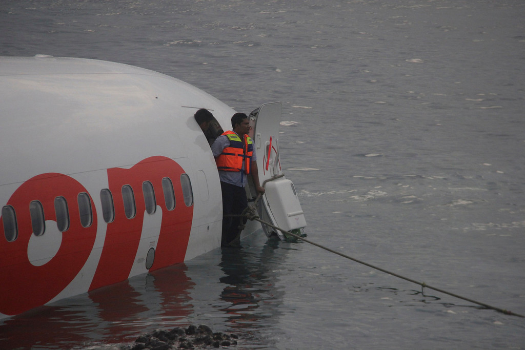 . A rescue worker stands at the door of a Lion Air plane that missed the runway in Denpasar, Bali in this picture provided by the Indonesian police April 13, 2013. All 108 passengers and crew miraculously survived when the Lion Air Boeing 737 missed the runway on the balmy Indonesian resort island of Bali on Saturday and landed in the sea. REUTERS/Indonesian Police/Handout