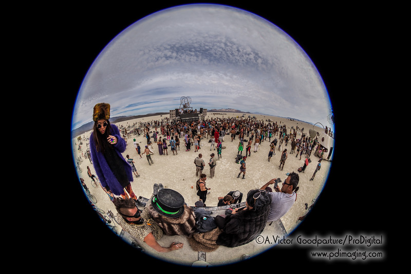 Two BLM Rangers watch over a surreal scene of revelers who have danced all night and into the morning on a dry lake playa in the middle of the Nevada desert.
