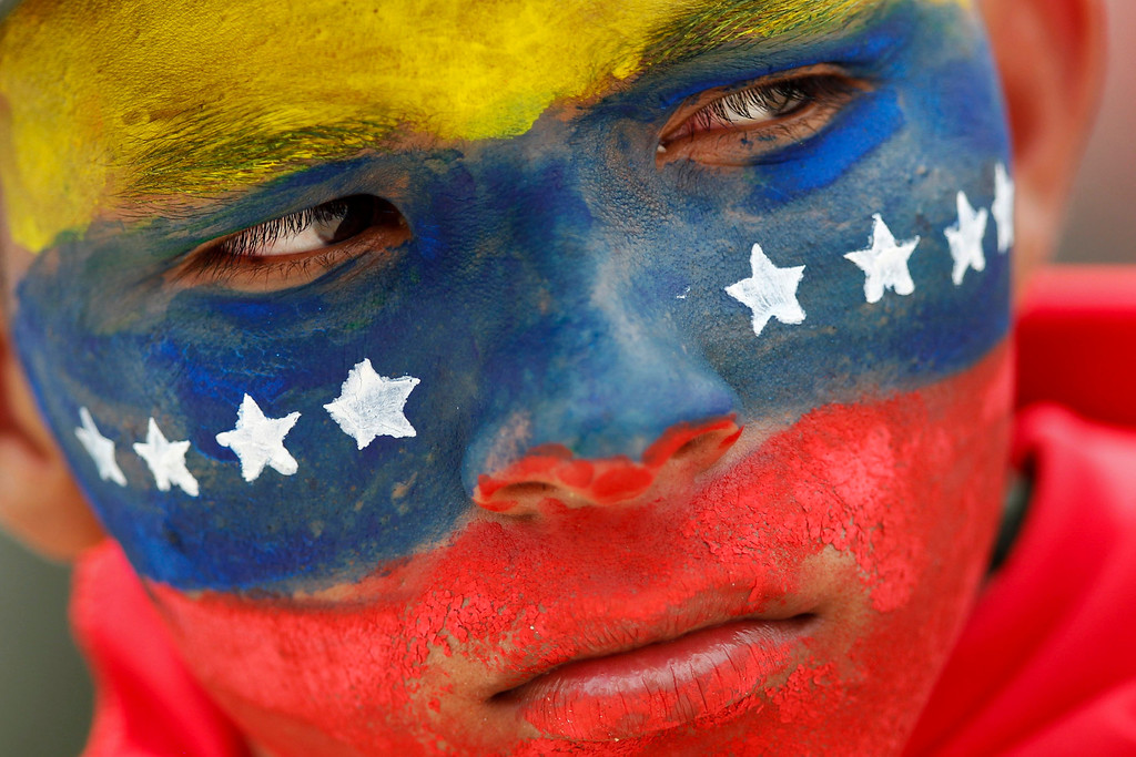 . A Venezuelan soldier, with his face painted with colours of the national flag, attends a military parade to commemorate the 21st anniversary of Venezuelan President Hugo Chavez\'s attempted coup d\'etat in Caracas February 4, 2013. Chavez is still in Cuba recovering from a cancer surgery and has not been seen in public since December 8 last year. REUTERS/Jorge Silva