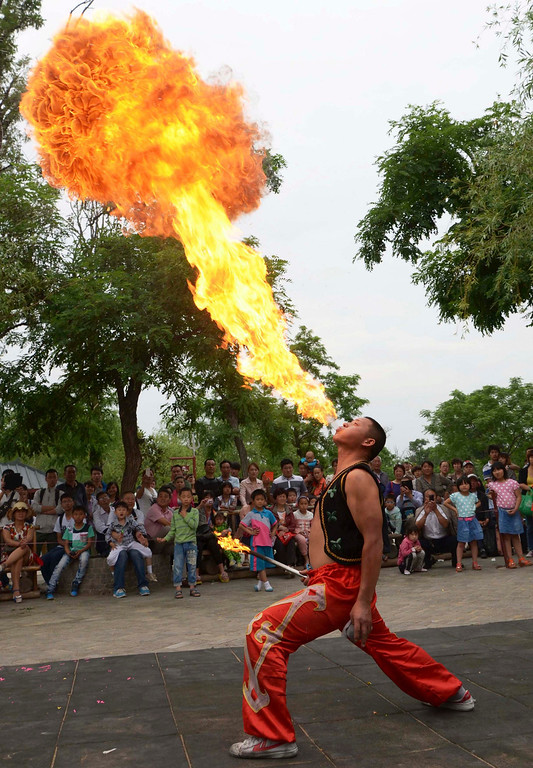 . Children and their parents watch as a folk artist breathes fire during a performance ahead of International Children\'s Day in Kaifeng, Henan province May 31, 2013. International Children\'s Day falls on June 1. Picture taken May 31, 2013. REUTERS/China Daily