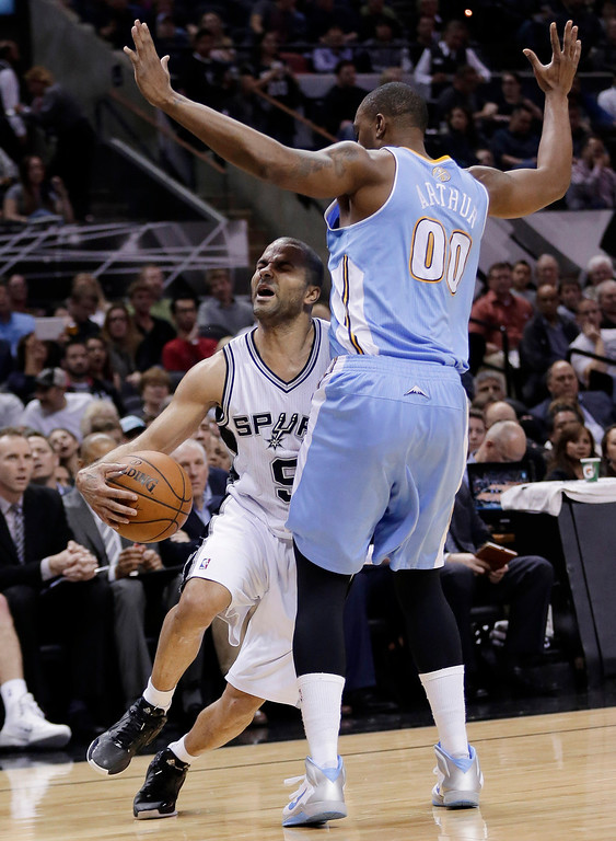 . San Antonio Spurs\' Tony Parker (9) runs into Denver Nuggets\' Darrell Arthur (00) as he tries to drive to the basket during the first half of an NBA basketball game, Wednesday, March 26, 2014, in San Antonio. (AP Photo/Eric Gay)