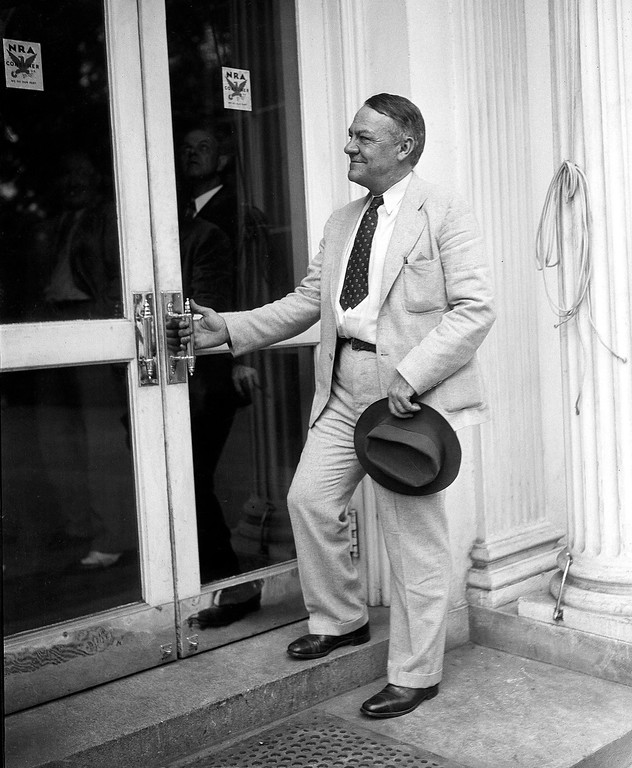 . 1933: Hugh Johnson. General Hugh S. Johnson, National Recovery Administrator, as he notes the NRA consumers insignia on the door of the executive mansion, Aug. 14, 1933. Johnson made the discovery on visiting the White House to confer with U.S. President Franklin Roosevelt on huge recovery program. (AP Photo)