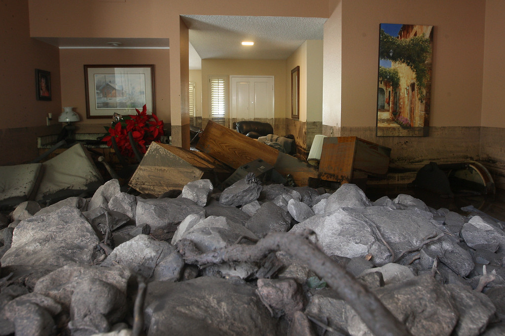 . A home is filled with rocks and mud after debris flows smashed into homes as a powerful storm that has been lashing northern California moves southward on December 12, 2014 in Camarillo Springs neighborhood of Camarilla, California. About two dozen homes were severely damage in a heavy pre-dawn downpour. Although water from the storm lowers the risk of wildfires and offers some short-term relief from the record drought conditions that are menacing the state, weather experts say it amounts to only a very small step toward ending the drought.   (Photo by David McNew/Getty Images)