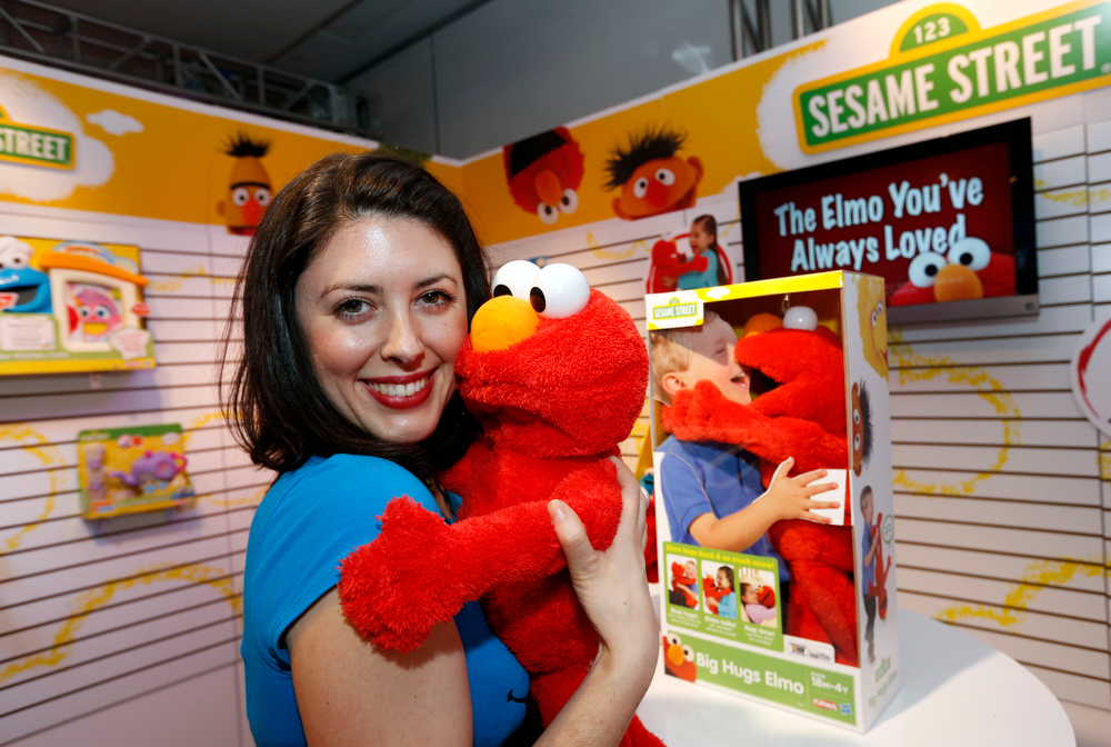 Description of . Demonstrator Patricia Santomasso welcomes BIG HUGS ELMO, Hasbroís first Elmo plush that really hugs kids back, to the PLAYSKOOL line with a hug in Hasbroís showroom at the American International Toy Fair, Friday, Feb. 8, 2013, in New York.  This cuddly 22-inch Elmo has flexible arms and a soft head to make him Hasbroís largest, cuddliest, most lifelike Elmo plush to date. (Photo by Jason DeCrow/Invision for Hasbro/AP Images)
