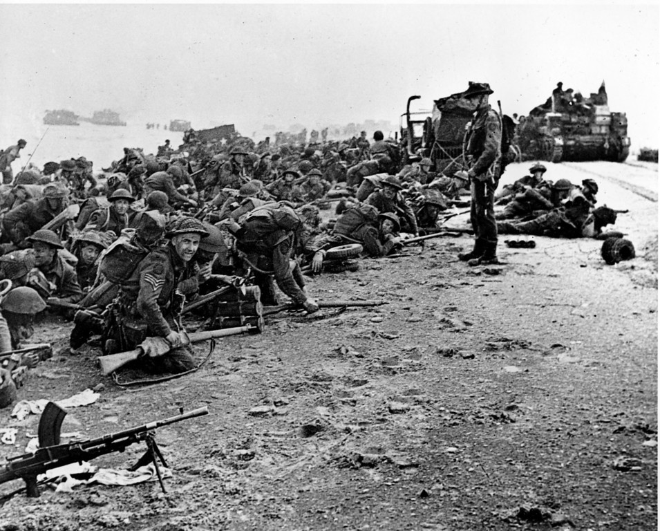 . After landing at the shore, these British troops wait for the signal to move forward, during the initial Allied landing operations in Normandy, France, June 6, 1944. (AP Photo)