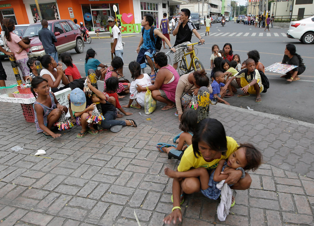 . Residents sit in the open air as they tap the pavement in a belief that the tremor would stop, following an aftershock of a 7.2-magnitude earthquake that hit Cebu city in central Philippines Tuesday. Oct. 15, 2013.  (AP Photo/Bullit Marquez)