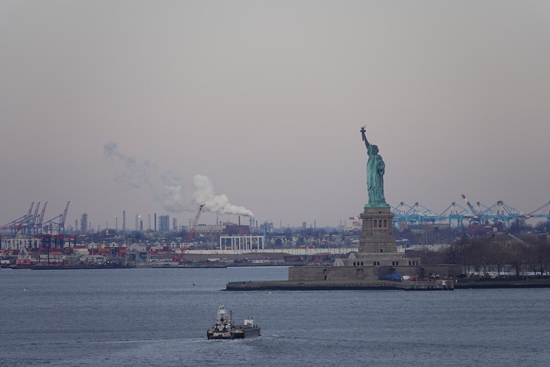 The Statue of Liberty from the Brooklyn Bridge with New Jersey and the container ports in the distance.