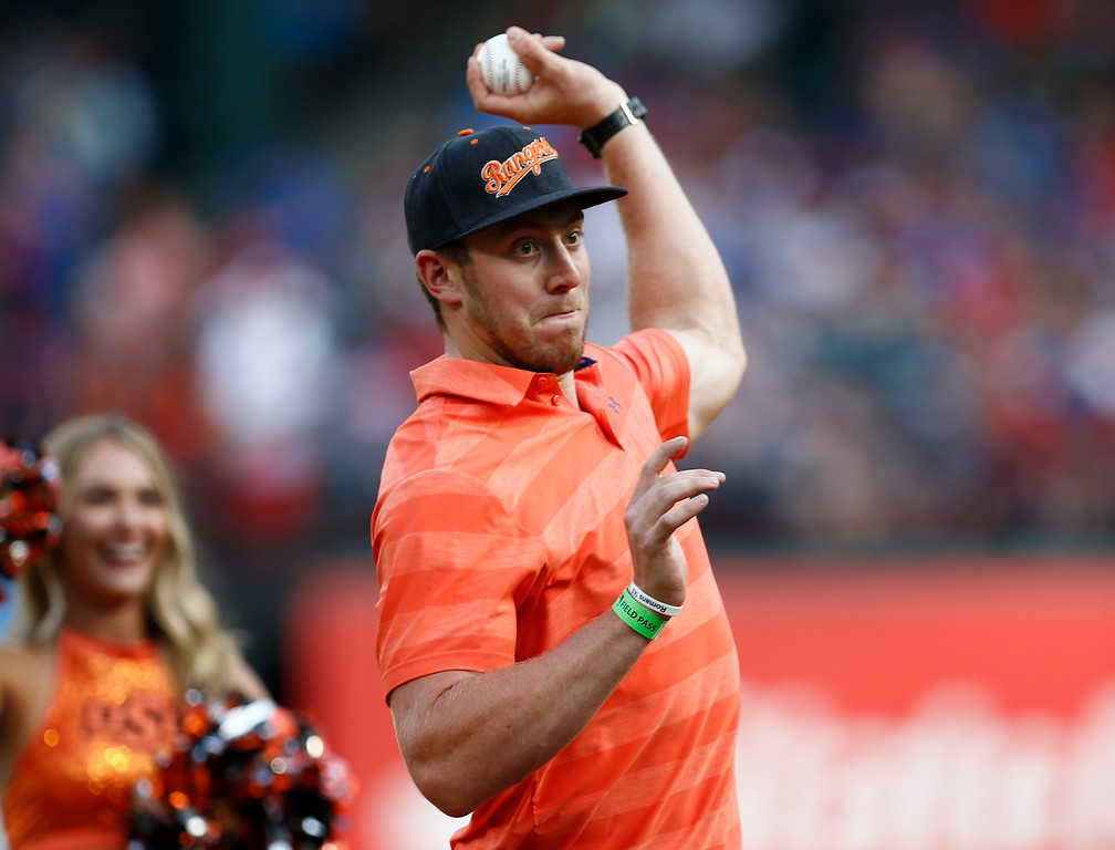 . Dallas Cowboys\' Blake Jarwin and OSU graduate throws out the ceremonial first pitch before a baseball game between the Cleveland Indians and the Texas Rangers, Saturday, July 21, 2018, in Arlington, Texas. (AP Photo/Jim Cowsert)