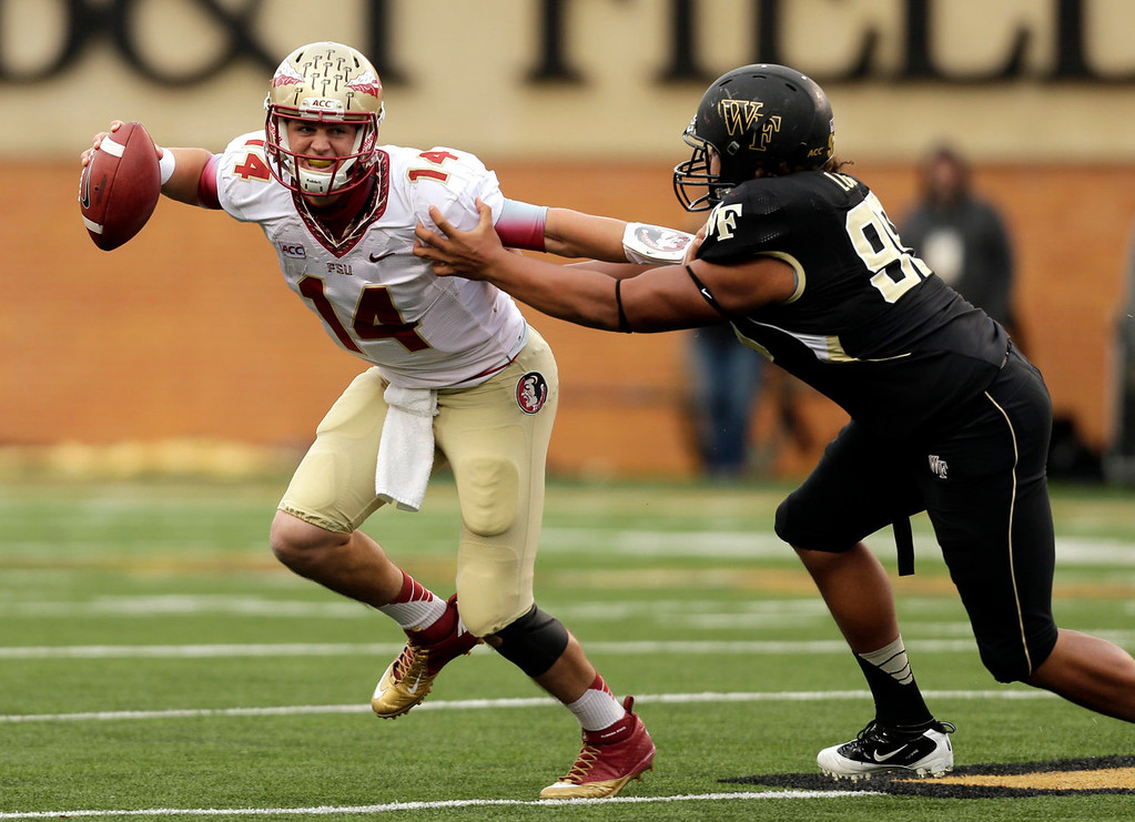 . Florida State quarterback Jacob Coker tries to avoid Wake Forest defensive end James Looney in the second half of an NCAA college football game in Winston-Salem, N.C., Saturday, Nov. 9, 2013. Florida State won 59-3. (AP Photo/Nell Redmond)