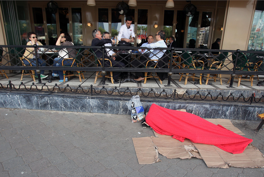 . A protester covered with a red blanket sleeps in front of a cafe as customers chat to each other at the Taksim square in Istanbul on Thursday, June 6, 2013. Turkish officials, scrambling to contain tensions, have delivered more conciliatory messages to thousands of protesters denouncing what they say is the government\'s increasingly authoritarian rule and its meddling in lifestyles. (AP Photo/Thanassis Stavrakis)
