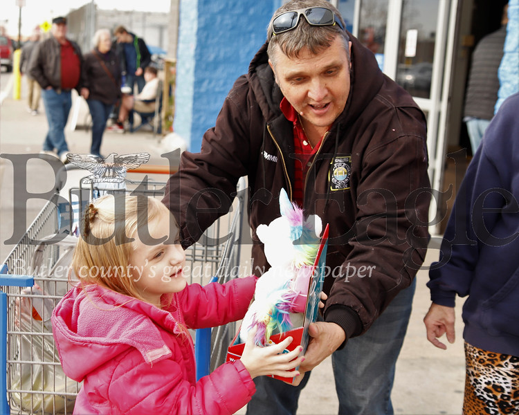 Jim Corll hands  his daughter Sadie a stuffed unicorn she picked out to donate to Toys For Tots Saturday. Seb Foltz/Bulter Eagle