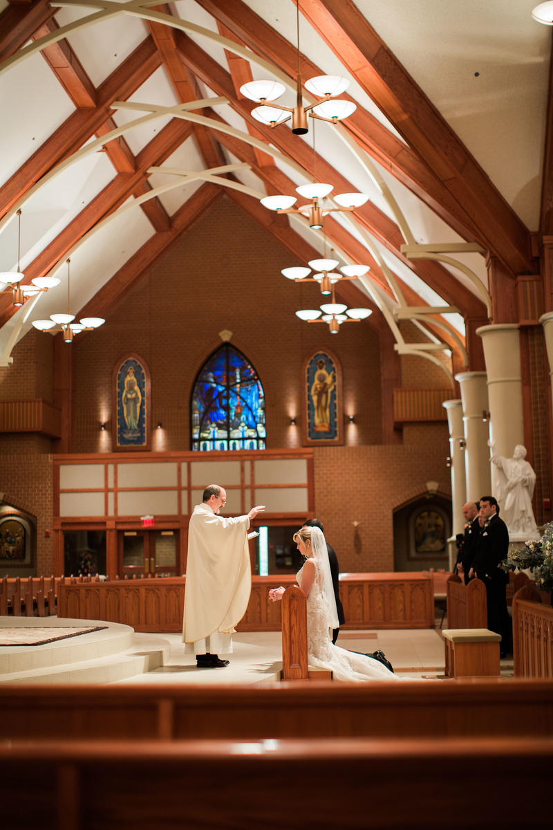 Priest prays over couple at their Catholic wedding ceremony before their Bluemont Vineyard wedding reception. Photos by the best Northern Virginia wedding photographer Jalapeno Photography. The Catholic wedding ceremony was at St. Theresa Catholic Church in Ashburn, VA.