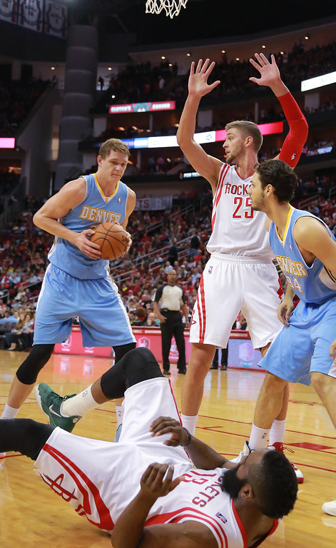 . Denver Nuggets center Timofey Mozgov looks to pass after knocking Houston Rockets guard James Harden to the floor as Rockets forward Chandler Parsons (25) and Nuggets guard Evan Fournier (94) watch during an NBA basketball game in Houston on Sunday, April 6, 2014. (AP Photo/Richard Carson)