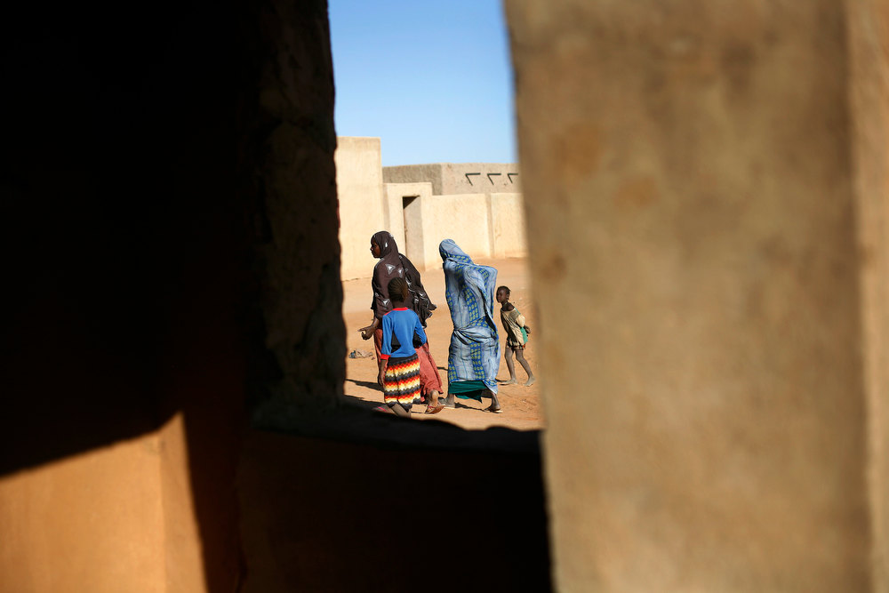 . Women and children walk past a madras in Gao, northern Mali, Thursday, Feb. 7, 2013. French troops began to withdraw from Timbuktu Thursday after securing the fabled city as they ramped up their mission in another northern Mali city, searching for Islamic extremists who may be mixing among the local population. (AP Photo/Jerome Delay)