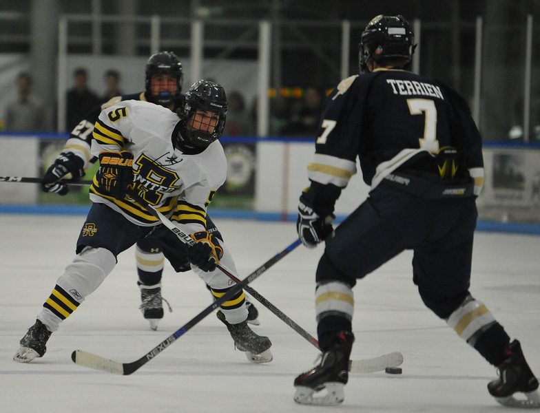 Rochester United's Drew Stempian (5) looks to shoot past Stoney Creek defenseman Ben Terrien (7) during the game played on Wednesday November 22, 2017 at the Onyx Ice Arena in Rochester Hills. RU lost to the Cougars 4-1. (Oakland Press Photo by Ken Swart)