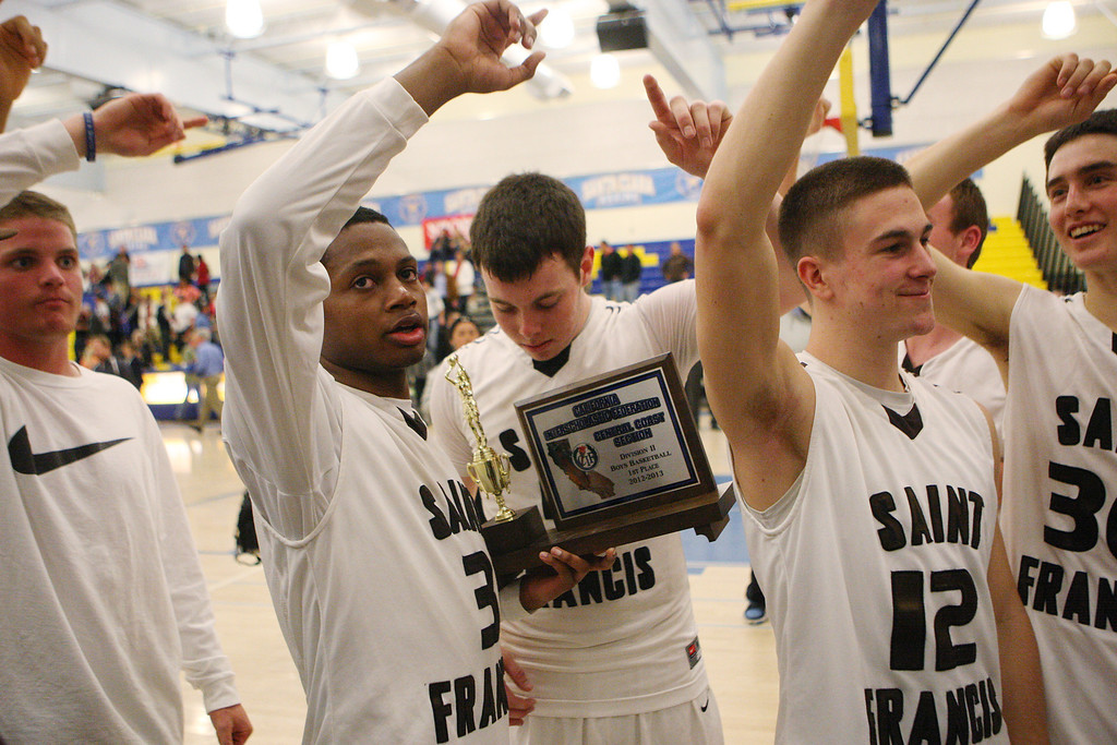 . St. Francis\' Khalid Johnson holds the CCS trophy as his team sings the school song after the game during the CCS Division II boys basketball finals at Santa Clara High School in Santa Clara, Calif. on Friday, March 1, 2013. The Saint Francis Lancers beat the Willow Glen Rams, 56-46. (Jim Gensheimer/Staff)