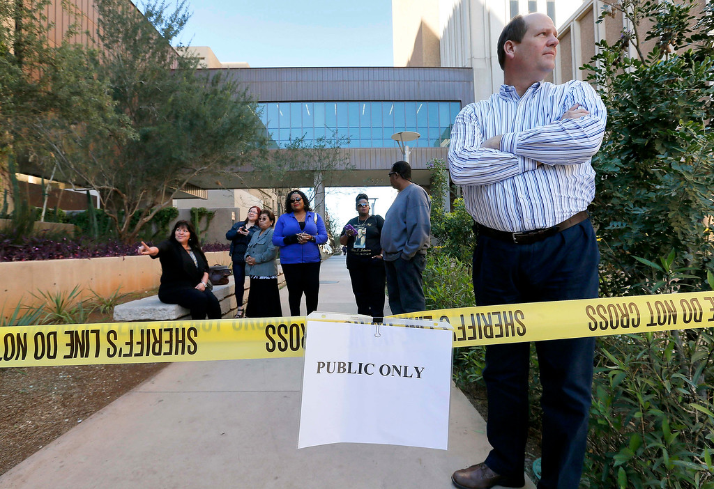 . A handful of onlookers wait outside the courthouse waiting for a Jodi Arias sentencing verdict, Thursday, March 5, 2015, in Phoenix. A judge declared a mistrial Thursday in the Jodi Arias sentencing retrial after a jury deadlocked on whether the convicted murderer should be executed or sent to prison for life for the 2008 killing of Travis Alexander.(AP Photo/Matt York)