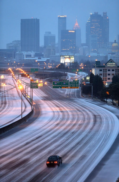 . A lone car makes its way north on Interstate 75-85 just south of downtown Atlanta, Georgia, USA early 12 February 2014, as an ice storm moves through the area leaving a thick layer of slush on roadways.  EPA/BEN GRAY